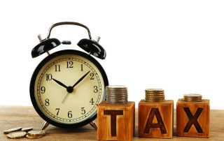 Tax time and alarm clock with coins on table